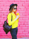 Fashion woman with cup of fruit juice over colorful pink bricks Royalty Free Stock Images