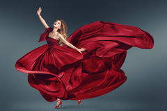 Fashion woman dancing in fluttering red dress royalty free stock photos