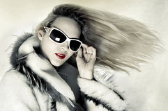 Fashion woman with developing hair. Fashion portrait of stunningly luxurious woman with long hair developing on wind and designer sunglasses Stock Images