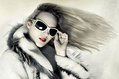 Fashion woman with developing hair. Fashion portrait of stunningly luxurious woman with long hair developing on wind and designer sunglasses Royalty Free Stock Photos