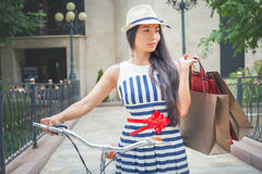 Fashion woman dressed in striped dress with bags Royalty Free Stock Images