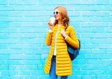 Fashion woman drinks coffee on a blue background. In the city Stock Photos