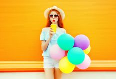 Fashion woman drinks a fruit juice holds an air colorful balloons Royalty Free Stock Photos