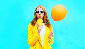 Fashion woman drinks fruit juice holds an orange air balloon Royalty Free Stock Photography