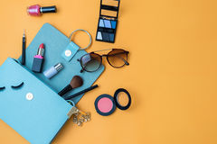 Fashion woman essentials, cosmetics, makeup accessories. Fashion woman essentials, cosmetics, cellphone, makeup accessories on colorful background, Top view stock photography