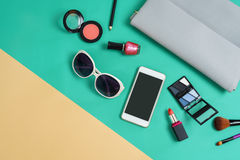 Fashion woman essentials, cosmetics, makeup accessories. Fashion woman essentials, cosmetics, cellphone, makeup accessories on colorful background, Top view Royalty Free Stock Photo