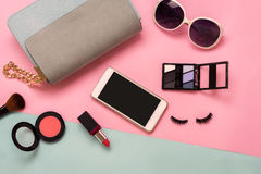 Fashion woman essentials, cosmetics, makeup accessories. Fashion woman essentials, cosmetics, cellphone, makeup accessories isolated on colorful background, Top Stock Photo