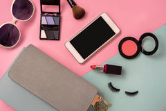Fashion woman essentials, cosmetics, makeup accessories. Fashion woman essentials, cosmetics, cellphone, makeup accessories isolated on colorful background, Top Stock Image