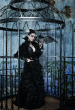 Fashion woman in fantasy dress posing in steel cage. Fashion model in fantasy dress posing in steel cage royalty free stock photography