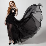 Fashion woman in fluttering black dress. White background. Royalty Free Stock Image