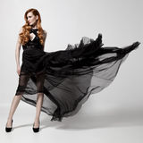 Fashion woman in fluttering black dress. White background. Stock Photos
