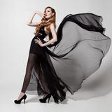 Fashion woman in fluttering black dress. White background. Stock Images