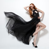 Fashion woman in fluttering black dress. White background. Royalty Free Stock Photography
