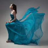 Fashion woman in fluttering blue dress. Gray background. Stock Image