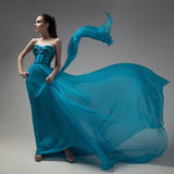 Fashion woman in fluttering blue dress. Gray background. Royalty Free Stock Photography