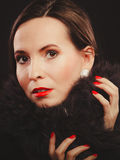 Fashion woman in fur coat, lady portrait. Fashion and beauty.  Woman in fur coat red lips and nails, lady retro style portrait on black background Royalty Free Stock Images