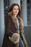 Fashion woman in fur coat on the street royalty free stock photography