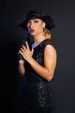 Fashion woman gangster style with handgun. Pistol on black background Royalty Free Stock Images