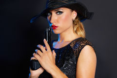 Fashion woman gangster style with handgun. Pistol on black background Stock Photos