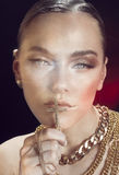 Fashion woman in golden jewelries. Mixed light Royalty Free Stock Photos