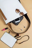 Fashion woman handbag with cellphone, makeup and accessories Stock Photo