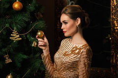 Fashion woman hanged a toy on the Christmas tree Royalty Free Stock Images