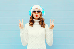 Fashion woman in headphones listens to music wearing a sunglasses, knitted hat, sweater over blue background, blowing lips Stock Image