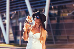 Fashion woman holding a sweet puppy Royalty Free Stock Photography