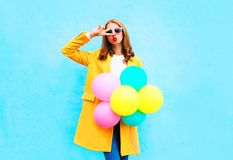 Fashion woman holds an air balloons in a yellow coat on colorful. Blue background royalty free stock images