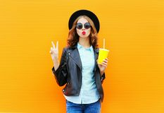Fashion woman holds a cup of fruit juice, black rock jacket in the city on a colorful orange Royalty Free Stock Photo