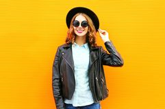 Fashion woman holds a cup of fruit juice, black rock jacket in the city on a colorful orange Stock Image