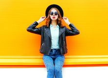 Fashion woman holds a cup of fruit juice, black rock jacket in the city on a colorful orange Royalty Free Stock Photography