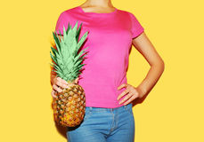 Fashion woman holds in hands pineapple over colorful yellow background Stock Images