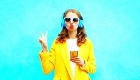 Fashion woman holds smartphone listens to music in headphones Stock Image