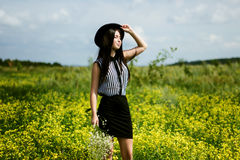 Fashion Woman In Black Hat Standing On Yellow Sunny Flowers Field Stock Image