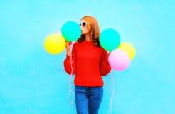 Fashion woman kisses an air colorful balloons on a blue Stock Photos