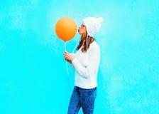 Fashion woman kisses an orange air balloon in a white hat on blue Royalty Free Stock Photo