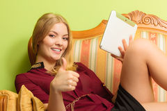Fashion woman laying on sofa with pc tablet. Stock Photos