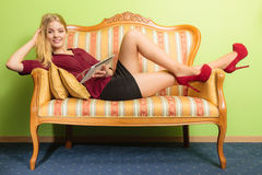 Fashion woman laying on sofa with pc tablet. Royalty Free Stock Photos