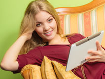 Fashion woman laying on sofa with pc tablet. Stock Photo