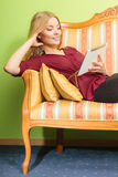 Fashion woman laying on sofa with pc tablet. Royalty Free Stock Image