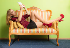 Fashion woman laying on sofa with pc tablet. Royalty Free Stock Photo
