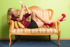 Fashion woman laying on sofa with pc tablet. Royalty Free Stock Images