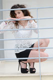 Fashion woman leaning against an iron railing Stock Photography