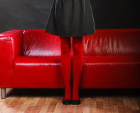 Fashion woman legs red pantyhose on couch Stock Photo