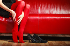 Fashion woman legs red pantyhose on couch Royalty Free Stock Photography