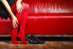 Fashion woman legs red pantyhose on couch Stock Images