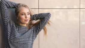 Fashion woman before light wall. Elegant blond woman touching her beautiful long hair as posing before big light building for fashion magazine shoot stock footage
