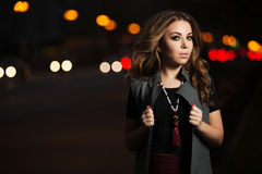 Fashion woman with long curly hairs on night city street Royalty Free Stock Photos