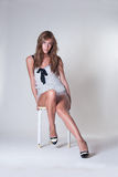 Fashion woman with long slim legs sitting on chair in studio with white paper Stock Photo